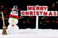 Snowman with a Merry Christmas signpost Stock Photos