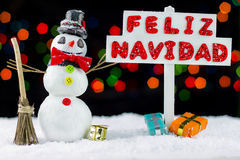 Snowman with a Merry Christmas signpost written on spanish Stock Image
