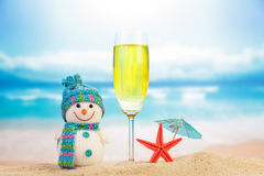 Snowman next to glass of champagne on the beach Royalty Free Stock Photos