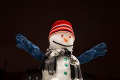 Funny snowman. Beautiful snowman in a red cap smiles and hands up. stock photos