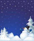 Snowman in a night winter forest. Snowman in snow-covered forest among fur-trees on a background of stellar sky Stock Image