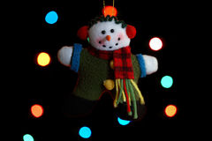 Snowman Ornament. An old fashioned, hand made, snowman ornament in front of holiday lights Stock Images