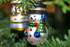 Snowman Ornament. Glass snowman ornament in Christmas tree Royalty Free Stock Images