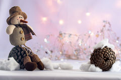 Snowman and pine cones. Christmas image with snowman, pine cones , snow and lights Stock Photo