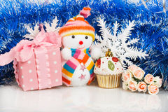 Snowman with pink gift box and white snowflakes Stock Photos