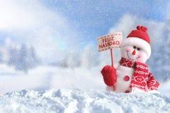 Snowman with a placard Feliz Navidad on the snow Stock Images