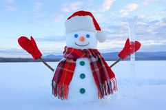 The snowman in plaid scarf, red hat, gloves. Amazing sunrise enlighten the sky. Nice landscape with the mountains. Winter day. The snowman in plaid scarf, red stock photo