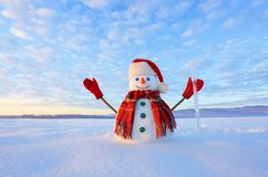 The snowman in plaid scarf, red hat, gloves and icicle in the hand. Amazing sunrise enlighten the sky. Nice landscape. The snowman in plaid scarf, red hat stock photo
