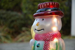 Snowman Portrait. Illuminated Christmas Snowman Ornament.  There are plants blurred in the background Stock Photos