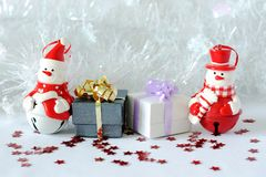 Snowman posed next to gifts with shiny knots on a Christmas holiday decor. A snowman posed next to gifts with shiny knots on a Christmas holiday decor Royalty Free Stock Photo