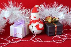 Snowman posed next to gifts with shiny knots on a Christmas holiday decor. A snowman posed next to gifts with shiny knots on a Christmas holiday decor Royalty Free Stock Photos