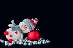 Snowman, a red ball, beads on black background. Royalty Free Stock Images