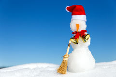 Snowman with a red cap, a golden bell and a boom in the snow Stock Photos