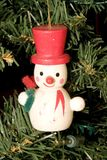 Snowman & red hat. A snowman with a red hat christmas tree decoration on the tree Royalty Free Stock Photo