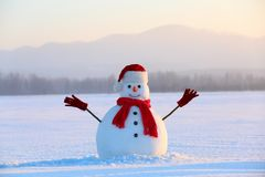 Snowman in red hat and scarf. Christmas scenery. High mountains at the background. Ground covered by snow. Nice cold winter day stock photography