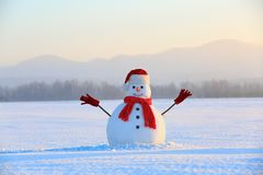 Snowman in red hat and scarf. Christmas scenery. High mountains at the background. Ground covered by snow. Nice cold winter day royalty free stock photo