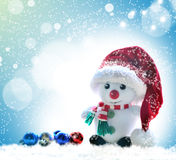 Snowman in red hat on a snowy background Royalty Free Stock Photography