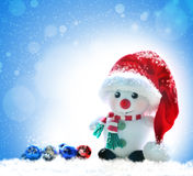 Snowman in red hat on a snowy background Stock Photo