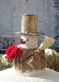 A snowman with a red rose in winter Stock Photos