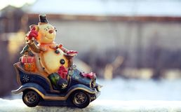 Snowman rides a car with gifts, Happy Holidays background Stock Photos