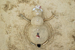 A snowman from sand and seashells on a beach. Royalty Free Stock Photos
