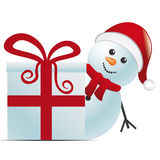 Snowman with santa hat behind gift Stock Photo