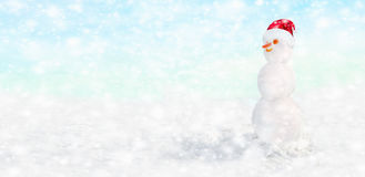 Snowman with Santa hat on his head under the snow Royalty Free Stock Images