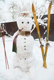 Winter Snowman with scarf and skiing. Christmas Snowman in hat with tobacco pipe . Stock Photo