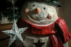 Snowman and shiny silver star under the christmas tree stock photo