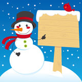Snowman Sign Post. Snowman pointing to a blank wooden sign post Royalty Free Stock Photography