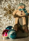 Snowman sits in a boot. The snowman sits in a boot, next to him Christmas balls and a candle Royalty Free Stock Image