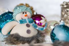 Snowman and Christmas balls. The snowman sits next to the Christmas balls of different colors Royalty Free Stock Photos