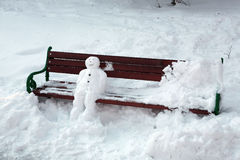 Snowman sitting on the bench Royalty Free Stock Photo