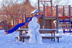 Snowman sitting on a bench. At a school playground Stock Image