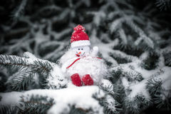 Snowman sitting on snow-covered branches of a Christmas tree Stock Photos