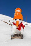 A snowman on a sled Royalty Free Stock Image