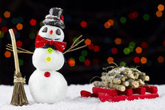 Snowman and sled on bokeh lights background Stock Photos