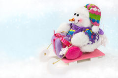 Snowman on a sled with a Christmas gift Stock Image