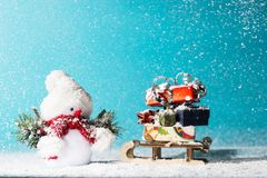 Snowman and sledge with christmas gifts on cyan background Stock Photos