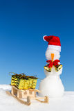 Snowman and a sledge with gifts in the snow Royalty Free Stock Photo