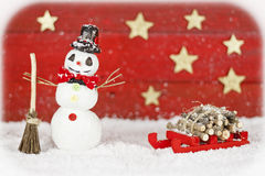 Snowman with sleigh on red background Stock Images