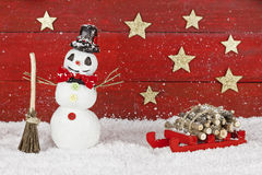 Snowman with sleigh on red background Royalty Free Stock Images