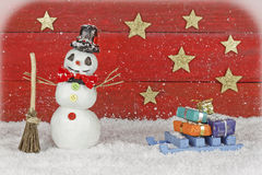 Snowman with sleigh on red background Stock Photo