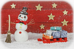 Snowman with sleigh on red background Stock Photos