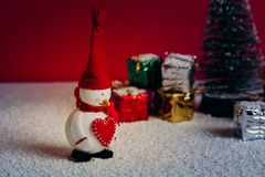 Snowman smiling close to a Christmas tree with gifts. Snowy floor and red background. Still life Christmas decoration with snowman, christmas tree, gifts, and a Royalty Free Stock Photography