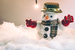 Snowman and snow is falling down, stand among pile of snow at silent night with a light bulb Royalty Free Stock Photography