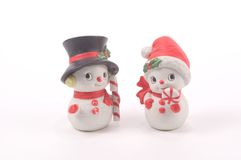 Snowman and Snow Woman. Christmas salt and pepper shakers in the shape of a snowman and snow woman holding peppermint candies and wearing seasonal hats Royalty Free Stock Photo
