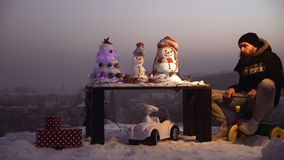 Snowman and snow xmas tree on winter landscape. Man in pilot glasses and hood on bike. Christmas and new year fun. Snowman and snow xmas tree on winter landscape stock footage