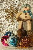 Snowman and snowflake. Snowman sits in a boot next to him Christmas balls and tinsel Stock Photo