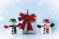Snowman stand near gift box on white background Stock Photos